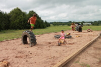 Children playing on a playground made out of tires in a big sandbox.