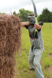 Man standing with bow and foam-tipped arrow drawn in a game of arrow tag.