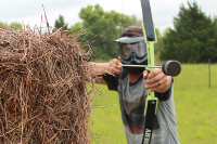 Man shooting a bow and foam-tipped arrow in a game of arrow tag.